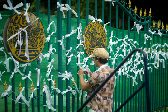 A pro-democracy protester ties white ribbons at the gate of Remand Prison in Bangkok