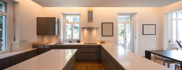 Modern kitchen in a period villa with window and parquet. White counters and brown doors