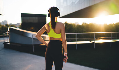 Back view of athletic girl with perfect muscular body shape enjoying workout break, rear of motivated sportswoman listening audio music via electronic bluetooth headphones for noise cancellation