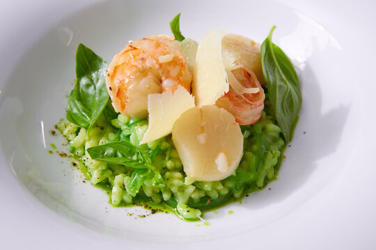 Delicious risotto with spinach, greens and prawns. Served in a modern dishware. Shallow dof