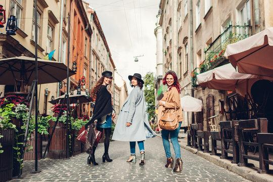 Stylish women walking on city street. Three girlfriends having fun in Lviv outdoors. Autumn fashion