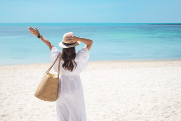 Happy traveler woman in white dress and hat enjoy beautiful sea view, young woman standing on sand...