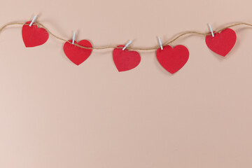 View of a heart necklace held by clamps on pink background