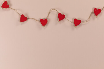 View of a heart necklace held by brown thread on pink background