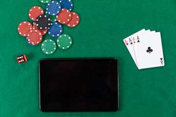 View of a black tablet, playing cards, a red dice and colorful tokens on plain green surface