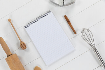 View of a composition with a notebook with cookie cutters, whisker and rolling pin on a white wooden