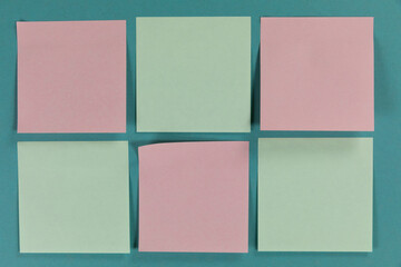 View of six green and pink sheets of paper in one size on plain blue background