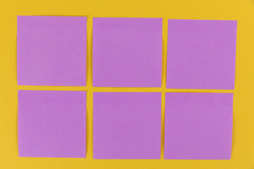 View of six purple sheets of paper in one size on a plain yellow background