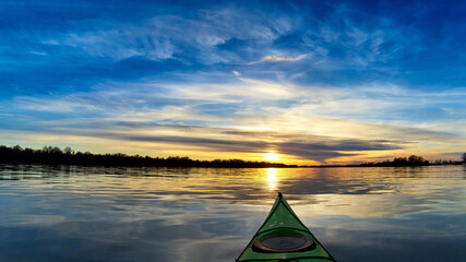 View from bow (prow) of green kayak at colorful sunset over Danube river at autumn time. Sky and...
