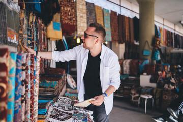 Cheerful tourist standing and choosing carpet