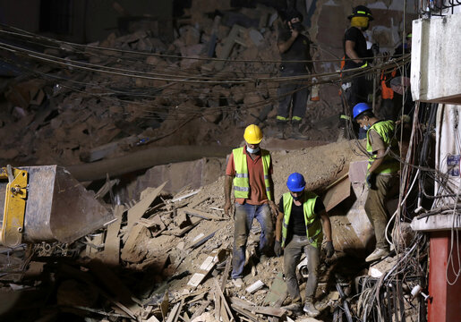 Lebanese civil defence members dig through the rubble of buildings which were collapsed by the explosion at Beirut's port area, after signs of life were detected