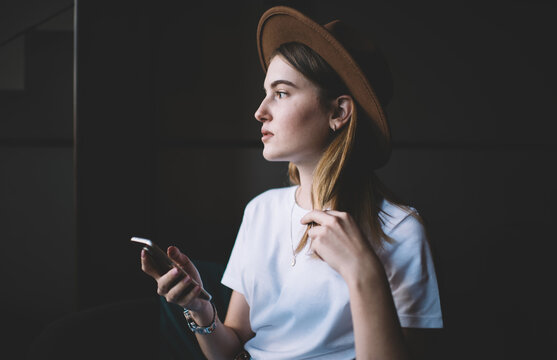 Thoughtful stylish lady in hat using smartphone in cafe