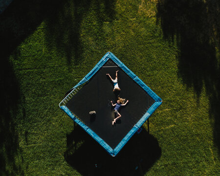 Aerial view of girls relaxing on trampoline