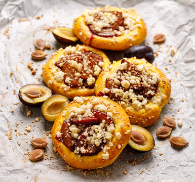 Yeast buns with plums, pumpkin  and crumble on baking paper close up view