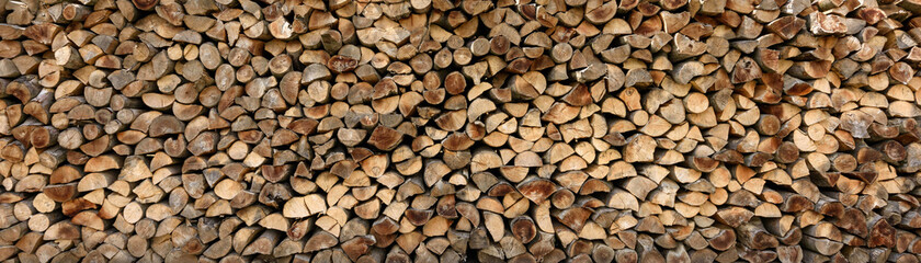 Photo sur Aluminium Texture de bois de chauffage Wall of firewood, background of dry chopped firewood. Alternative fuel concept. Wide angle shot of natural background. Panoramic image in banner format.