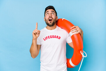 Young handsome lifeguard man isoalted pointing upside with opened mouth.