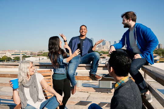 Group of young co-workers hanging out on rooftop patio laughing and having a drink, sharing images on mobile devices