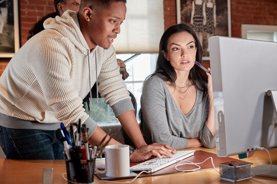 Group of young co-workers in office gathered around computer screen