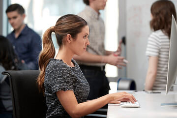 Young woman using computer in office typing on keyboard, co-workers having discussion around dry erase board in background
