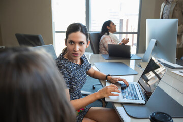 Woman taking to co-worker while working on laptop computer, other colleagues having discussion in background