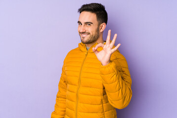 Young caucasian man isolated on purple background winks an eye and holds an okay gesture with hand.