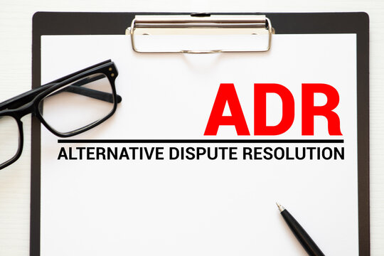Papers with title Alternative Dispute Resolution ADR on a table.