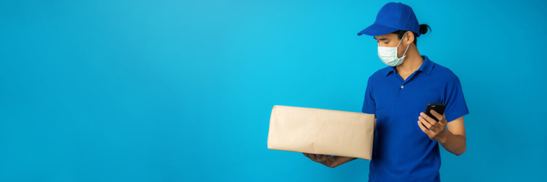 Asian delivery man wearing mask holding and check parcel box and phone on blue background in studio