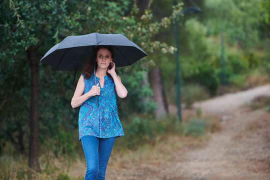 woman walking in the rain with black umbrella in rural setting