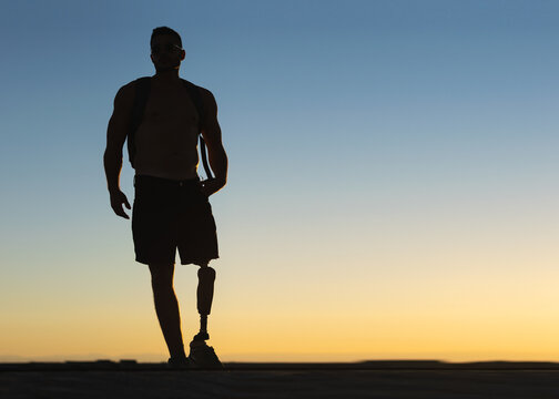 Silhouette of athletic man with prosthetic leg with sunset sky at background