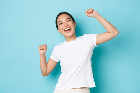 Portrait of successful winning, happy asian girl looking upbeat and celebrating, fist pump and dancing like champion, shouting yes delighted, standing blue background