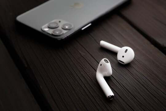Belgrade, Serbia - August 2020, Apple AirPods 2 and iPhone 11 Pro on wooden background