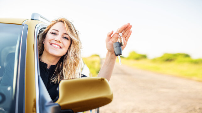 The woman driver shows the key to the car. Car purchase or rental.