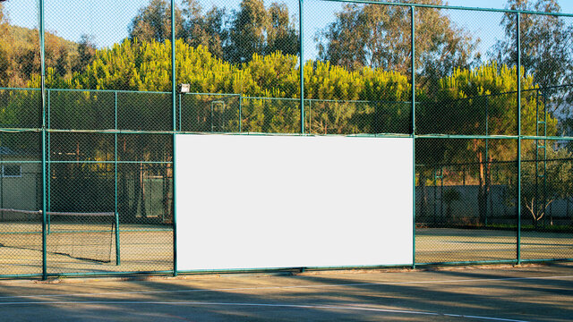 empty advertising white banner with mockup on iron fence on sport playground