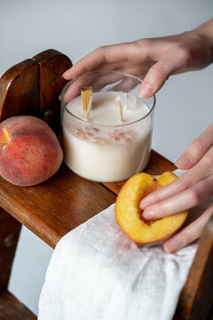 The candle is handmade from soy wax with the scent of peaches on a wooden stand. High quality photo