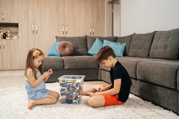 Funny, cute girl and boy playing lego at home on the floor, first education role lifestyle