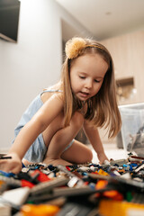 Funny, cute girl playing lego at home on the floor, first education role lifestyle