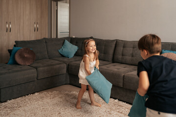 Two happy kids fighting with pillows at home. Happy childhood