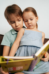 Bigger brother teaches his little sister to read while staying at home together