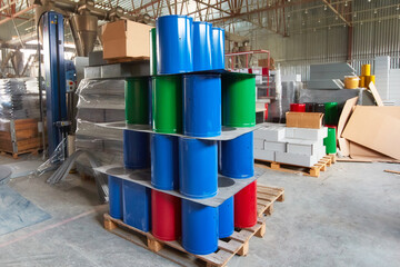 New trash bins are in the shop of the factory for the production of metal products . Blue, green and red metal containers for installation in urban environments and parks.