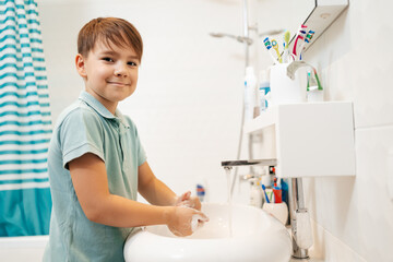 Preschool smiling boy Washing hands with soap under the faucet with water. Clean and Hygiene concept.
