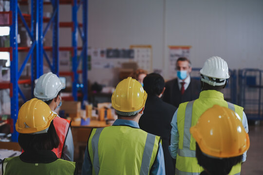 Manager and warehouse work team discuss preventive measures, spaced distance, wear anti-virus masks, workers in warehouse concept.