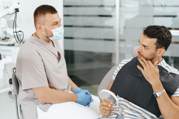 Male Dentist discussing with happy patient after treatment
