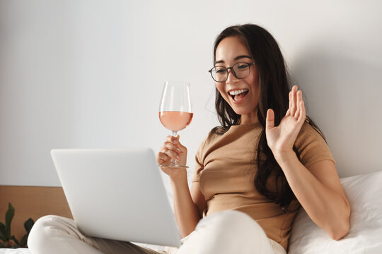 Portrait of happy attractive asian woman sitting on bed with glass of wine and having video call, waving hand at laptop, having online meeting or conversation while relaxing at home