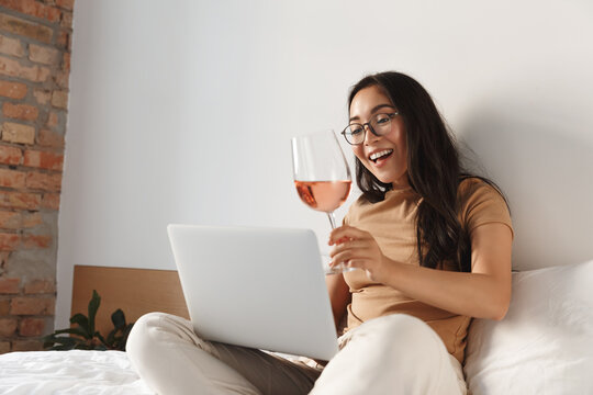 Portrait of cheerful asian girl on self-quarantine video-calling friends from home, sit on bed with glass of wine and laptop, talking to people on video conference, online drinking party