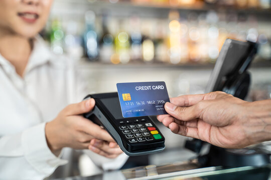 Customer using credit card for payment at cashier in cafe restaurant.