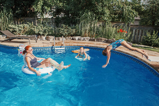 Mother with daughters children relaxing in swimming pool on home backyard. Sisters siblings diving and having fun in swimming pool together. Summer outdoors water activity for family and kids.