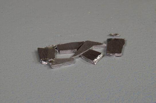 Small chips of the metallic element Beryllium (Be)