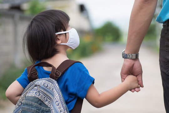 Little girl with backpack wearing cloth face mask hand in her father's hand waiting for school bus, back to school amid Coronavirus (COVID-19) pandemic.