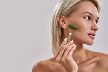 Close up portrait of young female blonde with perfect glowing skin looking aside while using jade facial roller for skincare and beauty treatment, posing isolated over grey background
