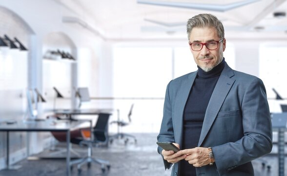 Business portrait - confident businessman in office. Trustworthy older man in his 50s with gray hair wearing glasses and jacket. Copy space.